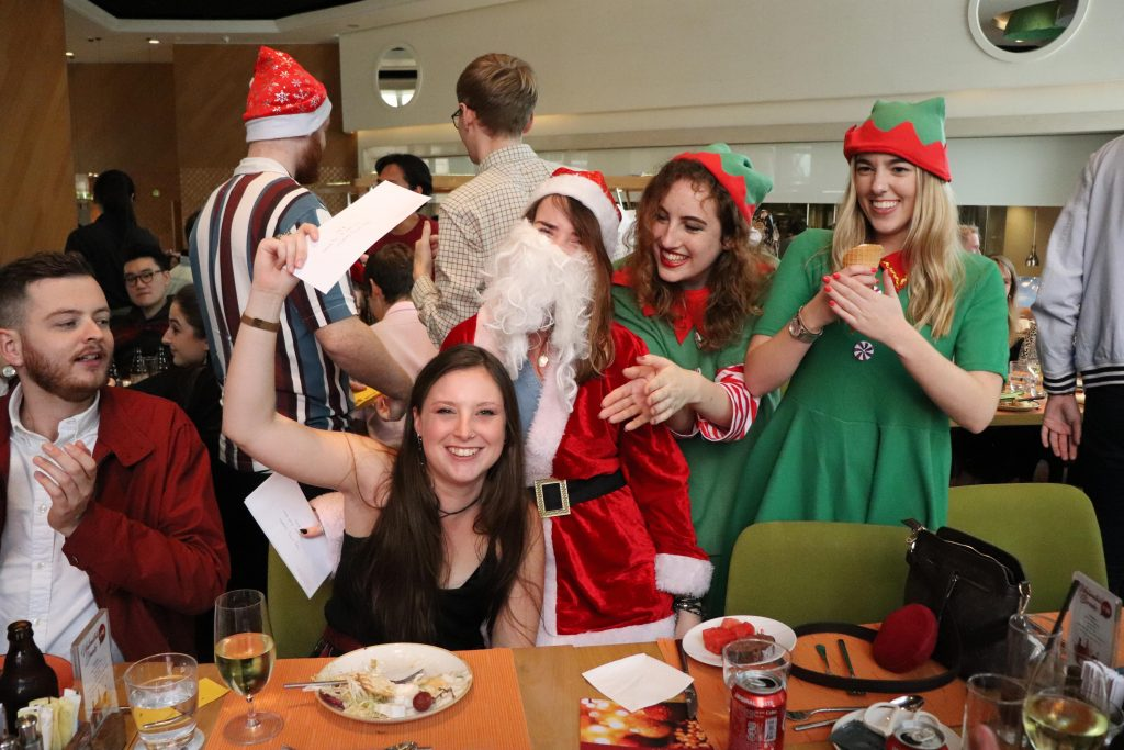 Tutors Patrick [left] and Elly [right] are joyous after receiving their gifts from Santa and the elves