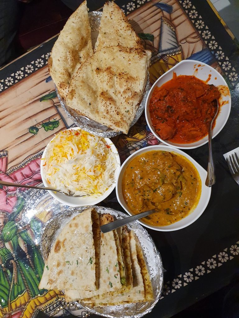 A feast of chicken madras, chicken vindaloo, pilau rice, garlic naan and keema naan at The Delhi Club   Image by Ben Chisem